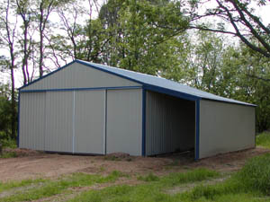 Gray and blue trimmed storage shed with enclosed car port